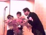 お孫さんから花束を受け取る加田氏